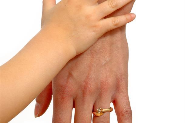 Foto: Barnehånd og en voksen hånd.