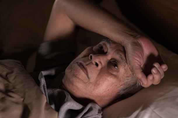 Older man lying in bed. Photo