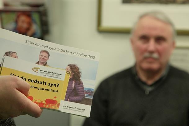 Brosjyrer fra Norges Blindeforbund vises frem til en person