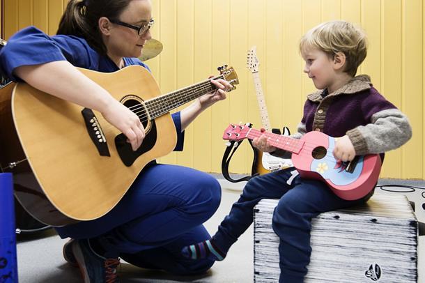 musikkterapeut og gutt spiller på hver sin gitar