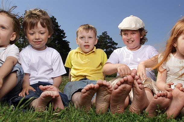 Gruppebilde barn sittende i gress. Foto
