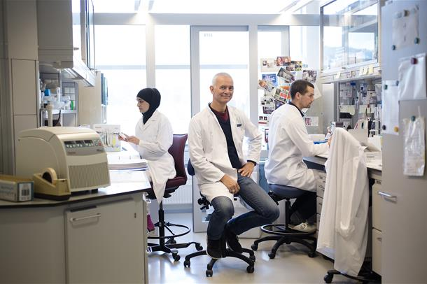 Foto. Tre forskere sitter på laboratoriet.