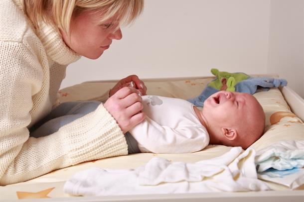 Mor med gråtande barn på stellebord. Foto