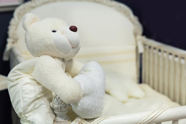 Teddybjørn ved tom babyseng. Foto