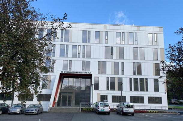 """Inngangsparti og fasade på bygning """"Overlege Danielsens hus"""". Blå himmel i bakgrunnen, biler på parkeringsplass foran bygning"""