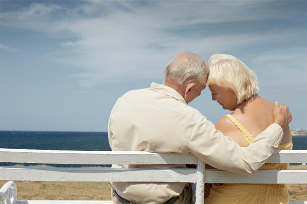 Eldre ektepar på benk ved sjøen