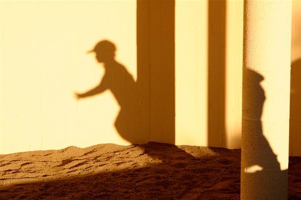 Skygge av gutt i solnedgang