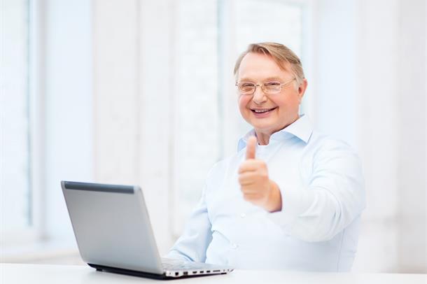Mann forran PC med tommel opp