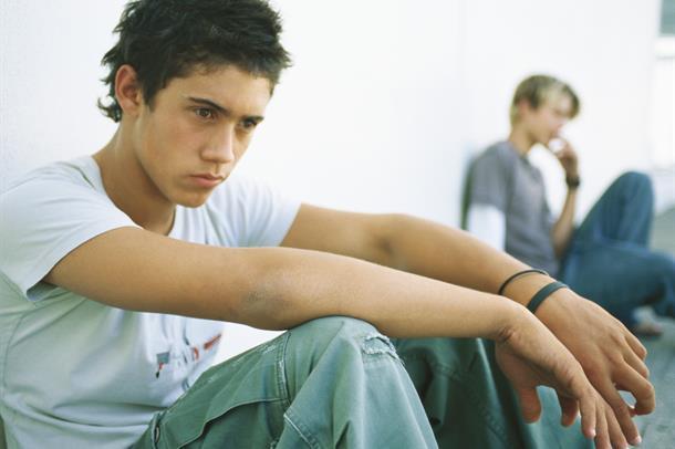 Tenåringsgutt sitter og ser