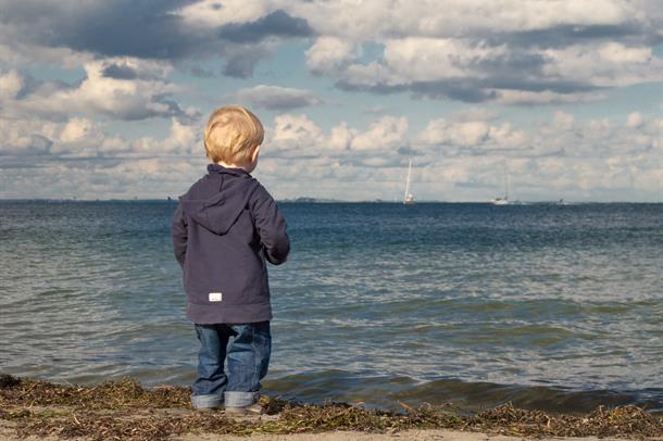 liten gutt ser ut over havet
