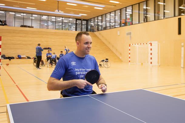 Mann i rullestol med bordtennisracket ved bordtennisbord i gymsal. Foto