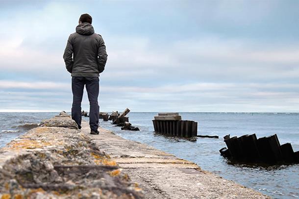 Mann ser ut mot havet. Foto