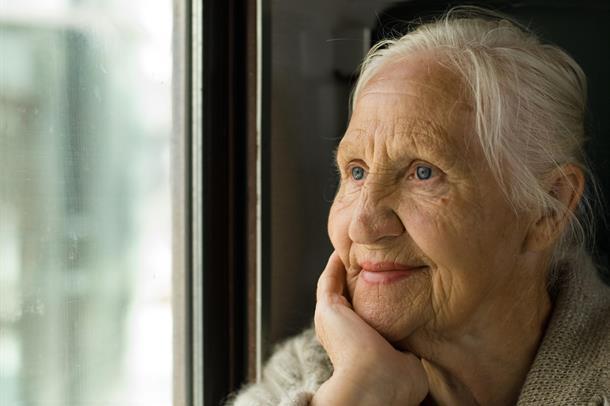 Eldre kvinne ser ut vindu. Foto